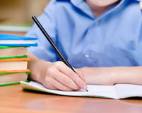 Mano con la escritura del lápiz en un cuaderno Imagen de archivo