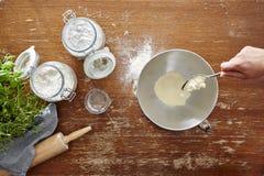 Mano con la farina di versamento del cucchiaio nella scena di cottura della ciotola sulla tavola di legno Fotografie Stock