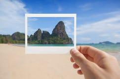 Mano con la foto de la playa Imagenes de archivo
