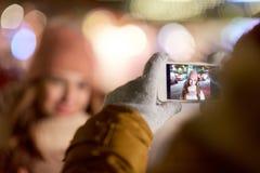 Mano con la imagen de la Navidad de la mujer en smartphone Imagenes de archivo