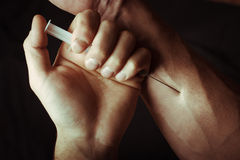 Mano con la jeringuilla de la heroína Fotografía de archivo libre de regalías
