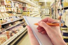 Mano con la lista de compras de la escritura de la pluma en supermercado Imágenes de archivo libres de regalías