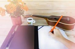 Mano con la matita, annotante sulla nota della carta in bianco con le ukulele Fotografie Stock