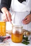 Mano con la miel de la cosecha del cazo de un tarro de miel Fotografía de archivo