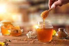 Mano con la miel de la cosecha del cazo de un tarro de miel Imagenes de archivo