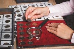Mano con la moneta, scatola con le monete raccoglibili nelle cellule e una pagina con le monete nelle tasche Fotografia Stock