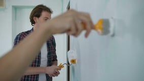 Mano con la parete della pittura del pennello in nuova casa stock footage