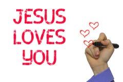 Mano con la parola Jesus Loves You di scrittura dell'indicatore fotografie stock