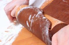 Mano con la pasta de amasamiento del rodillo para el pan de jengibre Imagenes de archivo