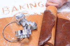 Mano con la pasta de amasamiento del rodillo para el pan de jengibre Foto de archivo
