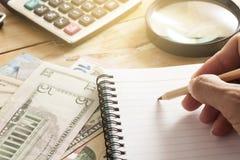 mano con la penna sul fondo dei soldi di affari Fotografie Stock