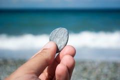 Mano con la piccola pietra sulla spiaggia immagine stock
