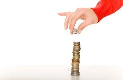 Mano con la pila de monedas Imagen de archivo libre de regalías