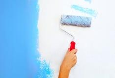 Mano con la pintura del cepillo del rodillo Imagen de archivo libre de regalías