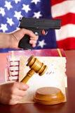 Mano con la pistola ed il martelletto dei giudici Immagini Stock Libere da Diritti