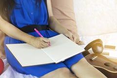 Mano con la pluma, anotando en el libro o el diario en blanco de trabajo Foto de archivo