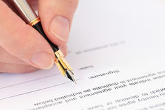 Mano con la pluma que firma un documento Imagen de archivo libre de regalías