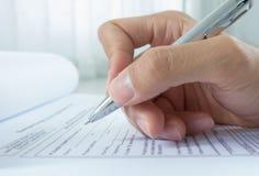 Mano con la pluma sobre formulario de inscripción Foto de archivo libre de regalías