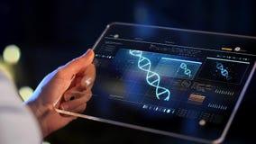 Mano con la proiezione virtuale del DNA sullo schermo della compressa video d archivio