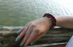 Mano con la pulsera cerca del mar Imagen de archivo