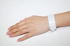 Mano con la pulsera paciente de la identificación Fotografía de archivo libre de regalías