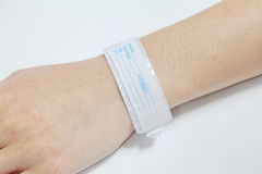 Mano con la pulsera paciente de la identificación Imágenes de archivo libres de regalías