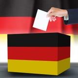 Mano con la scatola del ballotand sulla bandiera della Germania Fotografia Stock