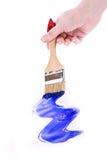 Mano con la spazzola e la vernice blu isolate immagini stock