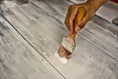 Mano con la tabla de madera blanca de la pintura del cepillo fotografía de archivo
