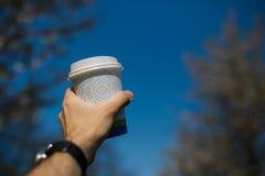 Mano con la tazza di caff? della carta - fiore di ciliegia variopinto di sakura in un parco a Riga, orientale - capitale europea  fotografia stock