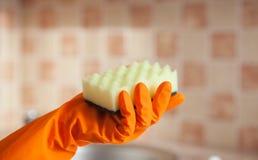 Mano con la ventana de goma de la limpieza del guante con la esponja Fotografía de archivo libre de regalías