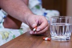 Mano con las medicinas en la mesita de noche Foto de archivo