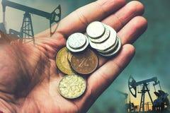 Mano con las monedas en el fondo de la producción petrolífera Concepto del negocio, extracción de recursos naturales fotos de archivo