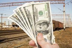 Mano con las notas de dólares contra el ferrocarril Foto de archivo