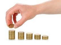 Mano con las pilas de las monedas Imagen de archivo libre de regalías