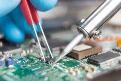 Mano con las pinzas que sostienen el microprocesador, soldadura del soldador él en el lugar Reparación del ordenador macrophotogr imagen de archivo libre de regalías