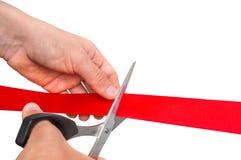 Mano con las tijeras que cortan la cinta roja - ceremonia de inauguración foto de archivo