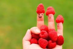 Mano con le dita felici che tengono i lamponi Fotografie Stock