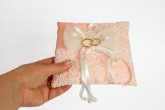 Mano con le fedi nuziali sul cuscino rosa di matrimonio fotografie stock