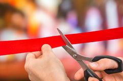 Mano con le forbici che tagliano nastro rosso - cerimonia di apertura Fotografia Stock