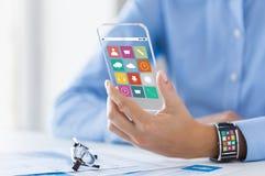 Mano con le icone di app sullo Smart Phone e sull'orologio Fotografia Stock