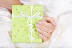Mano con le unghie dipinte che tengono un contenitore di regalo con l'arco Immagini Stock Libere da Diritti