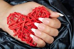 Mano con le unghie dipinte francesi artificiali lunghe che tengono un cuore Immagini Stock