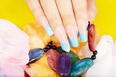 Mano con le unghie dipinte francesi artificiali lunghe che tengono una collana Fotografia Stock