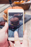 Mano con lo Smart Phone, prendente immagine dell'alimento dell'hamburger Fotografia Stock