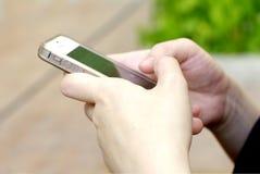 Mano con lo smartphone Fotografie Stock Libere da Diritti