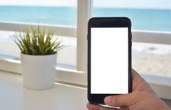 Mano con lo smartphone con lo schermo in bianco Fotografia Stock