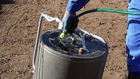 Mano con lo strumento del rullo del compattatore del suolo del materiale da otturazione del tubo flessibile dell'acqua Colpo stat stock footage