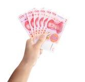 Mano con los billetes de banco chinos Imagenes de archivo