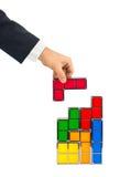 Mano con los bloques del juguete de los tetris Fotos de archivo